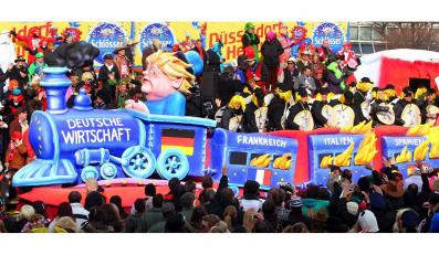 Angela Merkel pędzi płonącym pociągiem z nazwami krajów w kryzysie na paradzie w Dusseldorfie