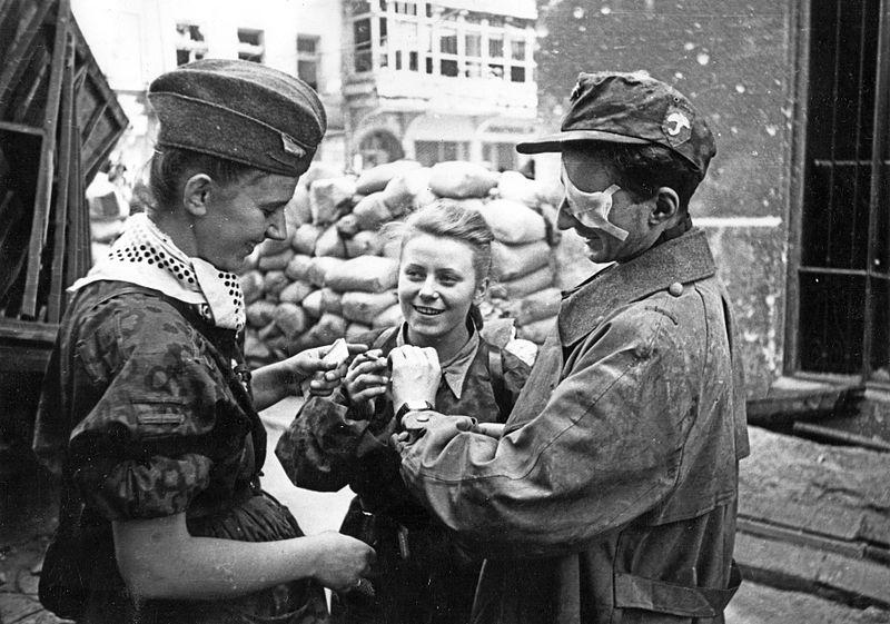 Maria Stypułkowska-Chojecka, pseudonim Kama (w środku), w czasie Powstania Warszawskiego. Wraz z drugą sanitariuszką opatruje rannego żołnierza AK z batalionu \