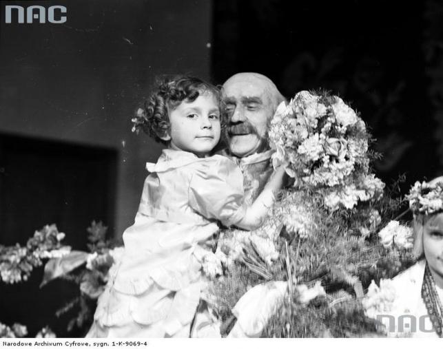 Ludwik Solski trzyma na rękach dziewczynkę wręczającą mu kwiaty podczas uroczystości jubileuszowej z okazji 60-lecia pracy scenicznej zorgnizowanej w Teatrze im. Juliusza Słowackiego w Krakowie (rok 1935)