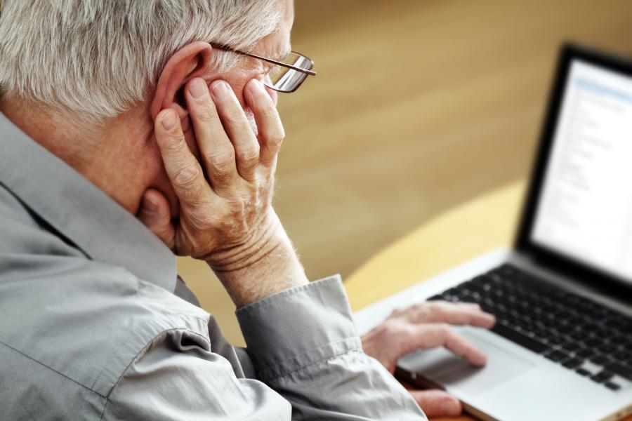 Senior pracuje przy komputerze