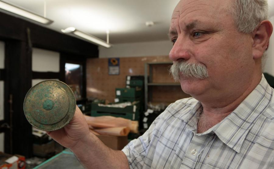 Stanisław Sinkowski z Muzeum Lubuskiego im. Jana Dekerta w Gorzowie Wielkopolskim prezentuje guz ozdobny z brązu