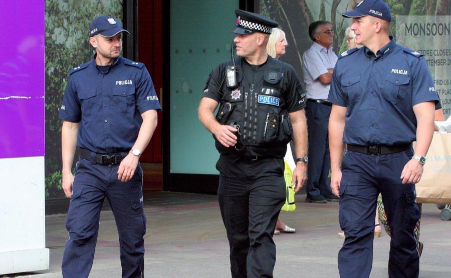 Polscy policjanci z Komendy Głównej Policji sierż. szt. Dariusz Tybura (P) i podkom. Bartosz Czernicki (L) wraz z brytyjskim policjantem patrolują ulice w Harlow